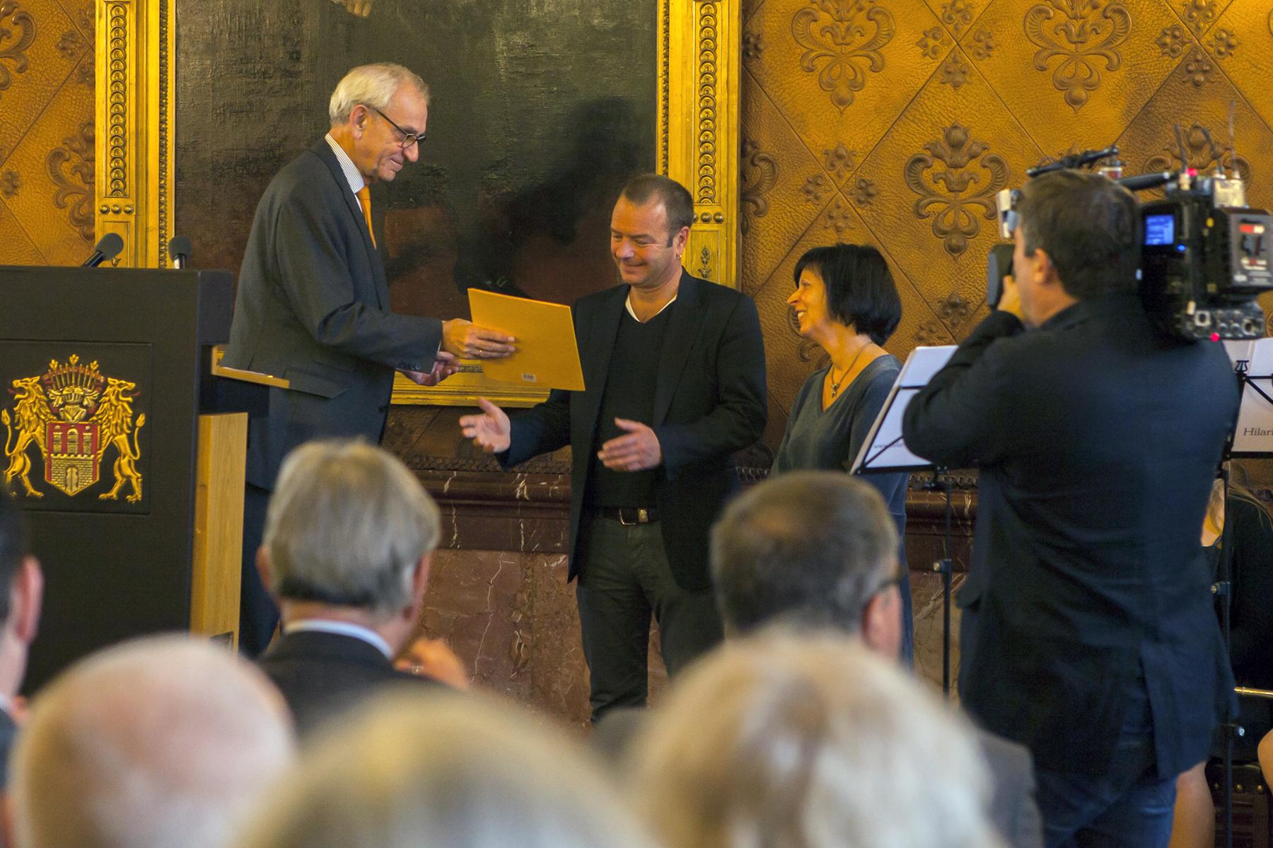 Hauptpastor em. Helge Adolphsen überreicht als Vorsitzender der Stiftungsjury den Yagmur-Erinnerungspreis 2016 an Petra Daszkowski und Jürgen Fiedler vom Arbeitskreis Dulsberg.